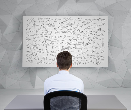 equations: student man looking to desk with athematics equations and formulas