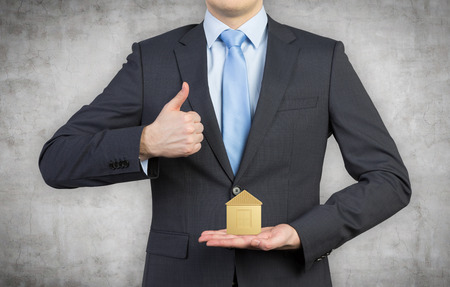 businessman showing thumb up and holding house photo