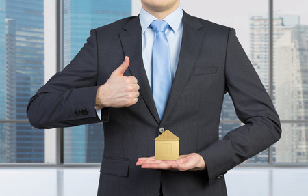 gold house: businessman showing thumb up and holding gold house Stock Photo