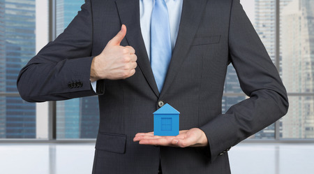 businessman showing thumb up and holding blue house photo