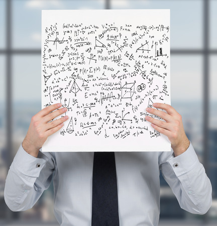 equations: businessman holding poster with mathematics equations and formulas