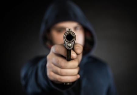 hombre disparando: asesino con el arma aislado en un fondo negro