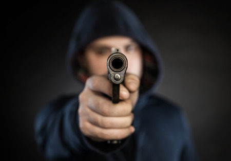crime: killer with gun  isolated on a black background