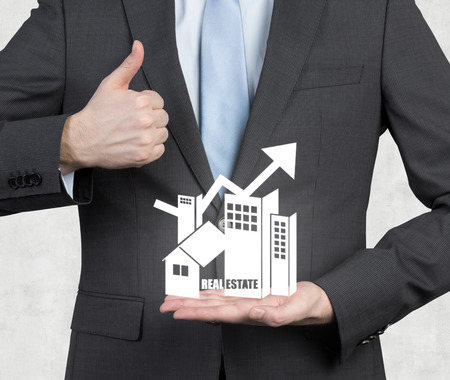 businessman showing thumb up symbol and holding real estate symbol photo