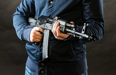 assault rifle: terrorist holding a rifle isolated on a black background Stock Photo