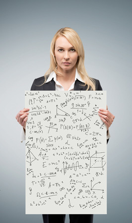 equations: woman holding poster with mathematics equations and formulas