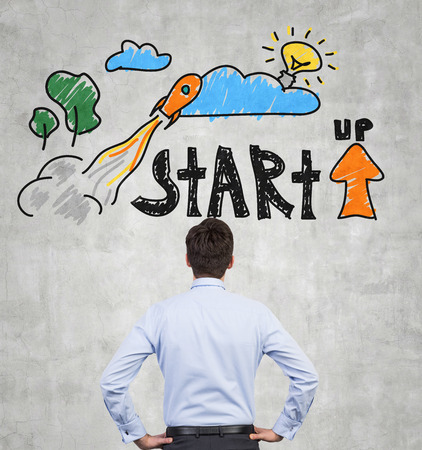 rocket man: businessman looking at drawing startup concept on wall Stock Photo
