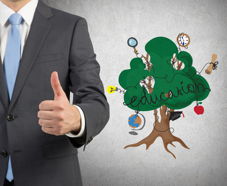 alumnus: businessman showing  thumb up and drawing education tree on wall