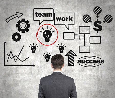stock predictions: businessman looking at teamwork concept on wall Stock Photo