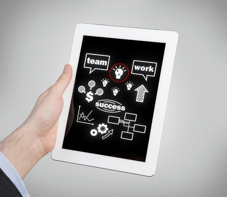stock predictions: hand holding tablet with teamwork concept on screen Stock Photo