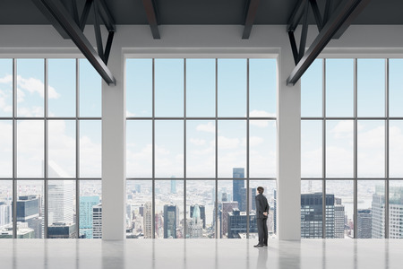 new york skyline: Businessman looking through the window in office. New York background Stock Photo