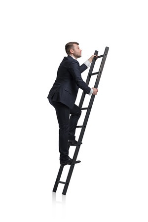 Young businessman is climbing to the career ladder. Isolated.