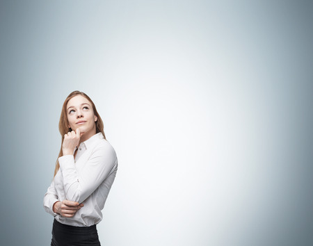 musing: Young business lady is thinking about something. Stock Photo