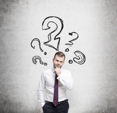 question marks: Young businessman is thinking about complicated questions. Stock Photo