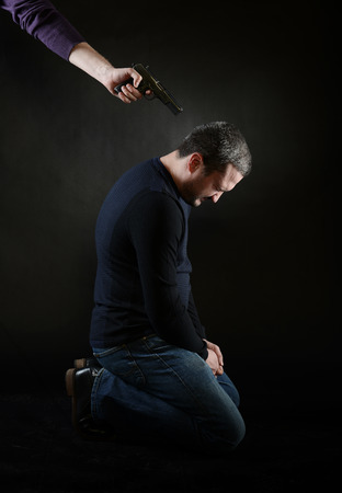 assassinate: A man on the knees under the gun Stock Photo