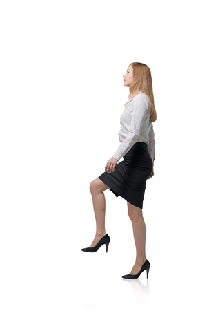 stepping on: Young businesswoman is going up. Isolated