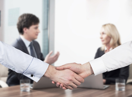shirtsleeves: Young couple at the business meeting. Handshake as a concept of successful deal.