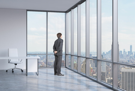 Young businessman is looking through the corner window. New York background.