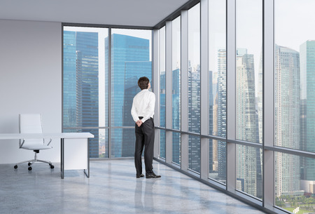 looking in corner: Young businessman is looking through the corner window. Singapore background.