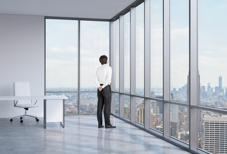 shirtsleeves: Young businessman is looking through the corner window. New York background.