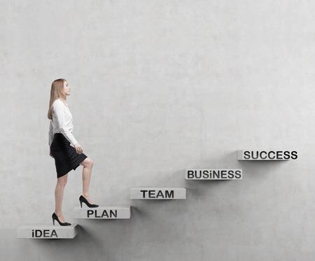 Junge Geschäftsfrau geht bis zu den Treppen. Ein Konzept für eine erfolgreiche Business-Projekt Standard-Bild