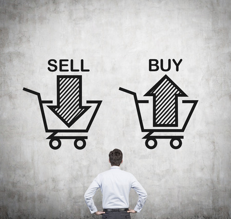 sell shares: Rear view of the businessman which is standing in front of the choice sell or buy