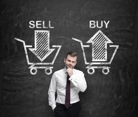 sell shares: Businessman is thinking about the choice sell or buy, arrows on the concrete wall. A concept of the trader who is forming a portfolio by selling and buying assets. Stock Photo