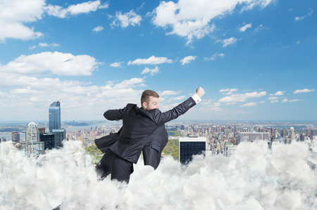 achiever: Businessman is flying over the central park in New York through the cloud