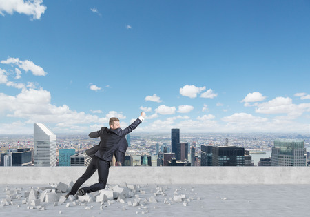 Businessman is flying up from the roof in New York. A concept of the success in career. Stock Photo