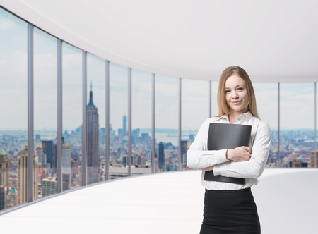 legal services: Young beautiful business lady is holding a black document case. New York panoramic office. A concept of legal services.