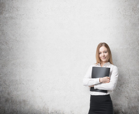 legal services: Young beautiful business lady is holding a black document case. A concept of legal services. Concrete background. Stock Photo