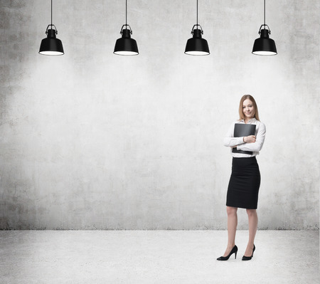 corporate executive: Young beautiful business lady is holding a black document case. Businesswoman is standing on the concrete office room. Stock Photo