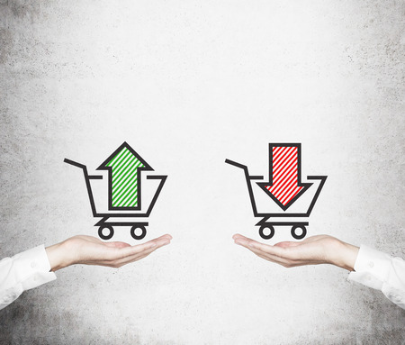 Hands offer the choice - sell or buy. Basket of goods. A concept of trading processes. Stock Photo