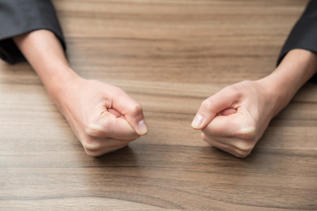 clenched: Closeup image of two businesswomans fists on a wood table