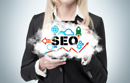 keywords link: Blonde businesswoman is holding a cloud as a metaphor of SEO