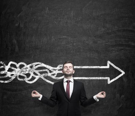 mente humana: Joven empresario meditativa está tratando de encontrar la mejor solución para el desarrollo de negocios. Una flecha como símbolo de la manera rápida de la aplicación de las ideas innovadoras. Tiza fondo de la pared. Foto de archivo
