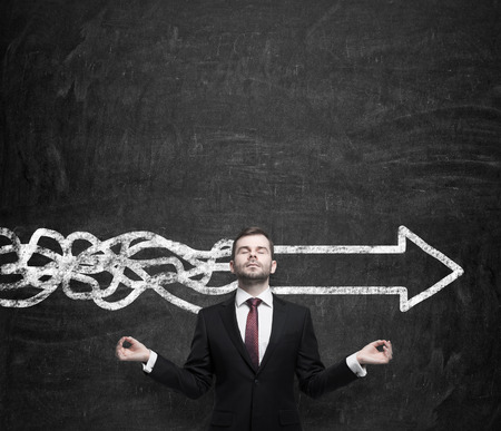 Meditative young businessman is trying to find the best solution for business development. An arrow as a symbol to the fast way of the implementation of the innovative ideas. Chalk wall background.