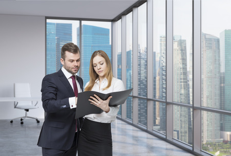 signing authority: A young business couple are looking at the black document case in a modern panoramic office. Singapore cityscape. A concept of the teamwork.