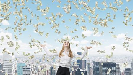 Schöne blonde Geschäftsfrau freut sich über fallende Dollar-Noten vom Himmel.