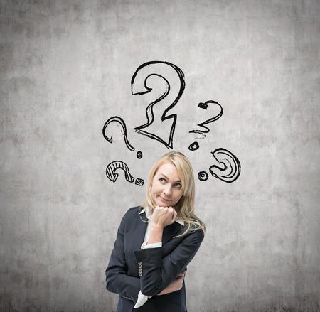 onbeantwoorde: Mooie zakelijke vrouw is na te denken over client services oplossingen. Getrokken vraagtekens op de betonnen muur.