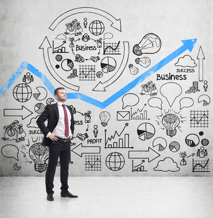 optimisation: Confident handsome businessman is thinking about further business development. Business optimisation flowchart on the concert wall. Stock Photo