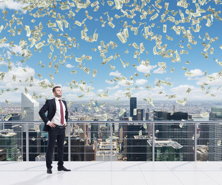 Confident handsome businessman is standing on the roof terrace in New York City. Falling dollar notes from the sky. A concept of financial consultancy. Stock Photo