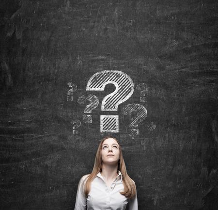 interrogativa: Hermosa mujer de negocios est� pensando en soluciones de servicios de cliente. Dibujado signos de interrogaci�n en el muro de hormig�n oscuro.