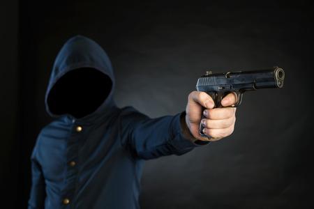 vengador: Persona armada en una sudadera con capucha est� apuntando un arma de fuego al objetivo.