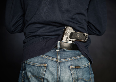 Hided handgun under the denim belt. Stock Photo