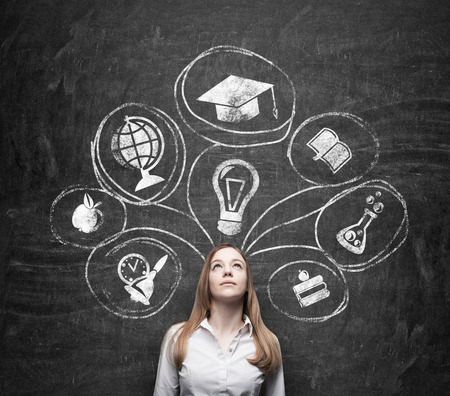 business degree: Young beautiful business lady is thinking about getting degree at the university. Drawn the range of the educational icons over the dark concrete wall. Graduation hat. Stock Photo