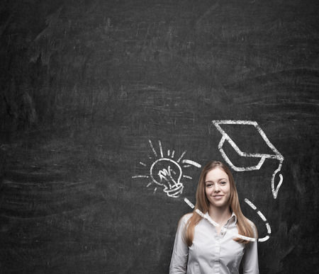 insightful: Young beautiful business woman is thinking about education at business school. Drawn graduation hat and light bulb over the concrete wall. A concept of the usefulness of business education.