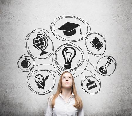 教育: 年輕漂亮的業務小姐是想獲得學位的大學。繪製的教育圖標在混凝土牆的範圍內。畢業的帽子。