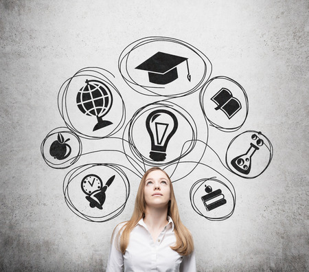 education icon: Young beautiful business lady is thinking about getting degree at the university. Drawn the range of the educational icons over the concrete wall. Graduation hat. Stock Photo