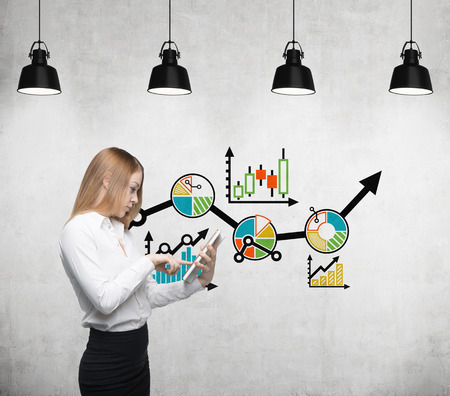 economist: Young beautiful business woman is thinking about business optimisation process by working on the tablet. Drawn colourful business flowchart on the concrete wall. Stock Photo